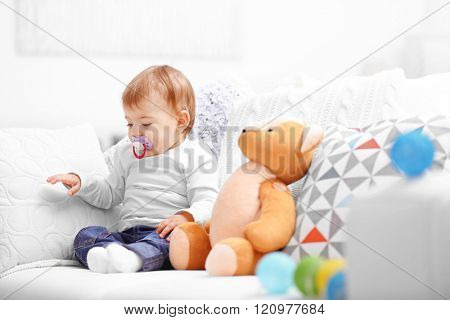 Sweet baby girl with a soother sitting on a sofa