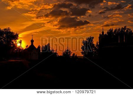 Two Churches Between Trees Silhouetted During Sunset