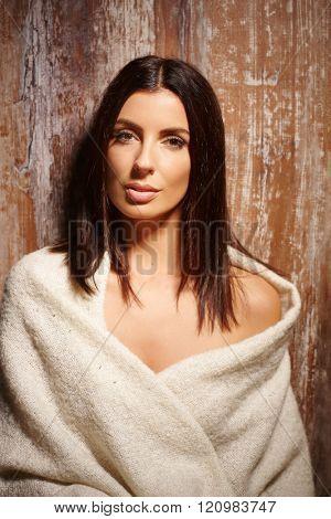 Portrait of beautiful sensual woman in blanket, looking at camera.