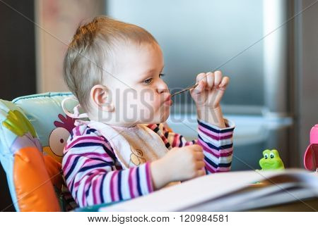 The Child Sits In A High Chair And Holding A Spoon In His Mouth