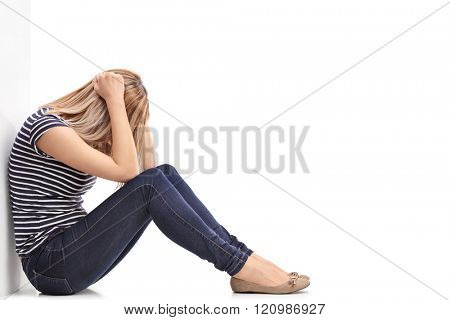Depressed blond woman sitting on the floor with her head down and leaning against a wall isolated on white background