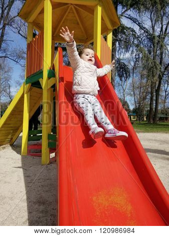 Vertical shot of an excited baby girl sliding down a slide at a playground outdoors