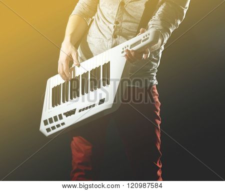 Male hands with synthesizer on dark background