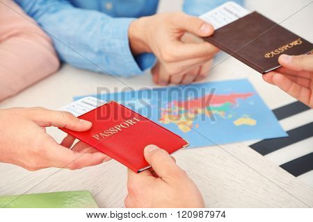 Agent giving passports and tickets to customers in the office of travel company