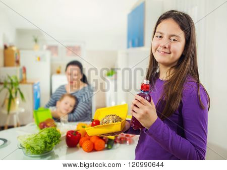 Girl With A Box For A Snack In The Kitchen