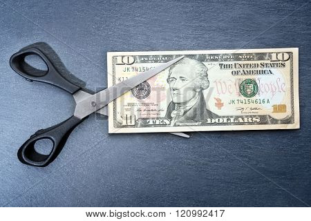 Concept of spending money - scissors cut money on black background