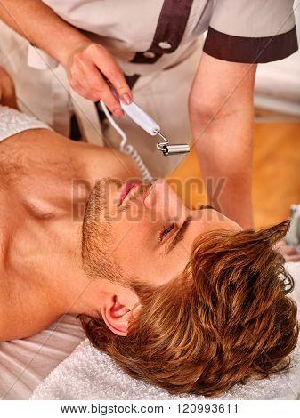 Man enjoying electric galvanic face and neck spa massage at beauty salon.