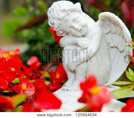 Grave angel between flowers