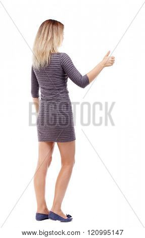 Back view of  woman thumbs up. Rear view people collection. backside view of person. Isolated over white background. The girl in the brown dress right hand shows a gesture of approval.