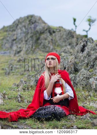 Beautiful Blonde Woman In Old-fashioned Dress And Red Cloak Sitting On The Rocks