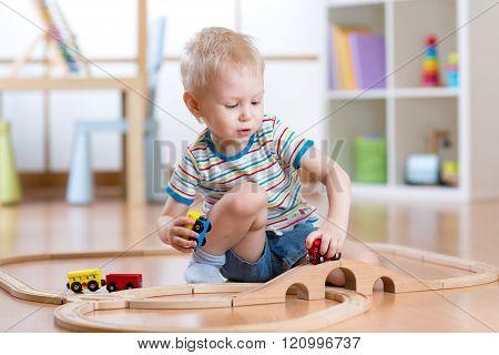 Child boy playing rail road toy in nursery