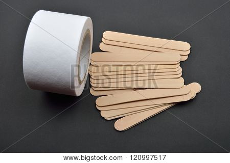 Picture Of Many Wooden Spatulas And Roll Of Paper For Wax Depilation On Black Background