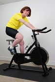 stock photo of exercise bike  - woman working out on an exercise bike in a home gym  - JPG