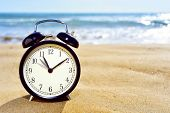 ������, ������: closeup of an alarm clock on the sand of a beach adjusting forward one hour at the beginning of the