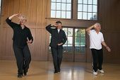 stock photo of tai-chi  - Three seniors practicing Tai Chi indoors - JPG