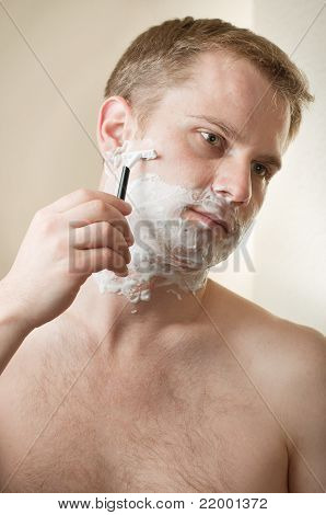 Portrait of a young man shaving