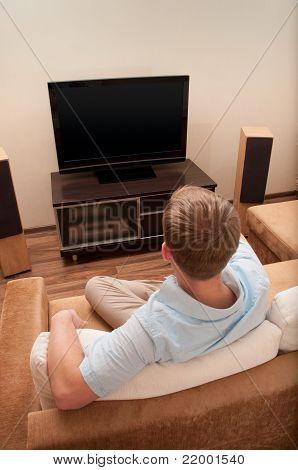 Man lying on sofa watching TV at home.