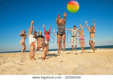 Group of young joyful people playing volleyball on the beach
