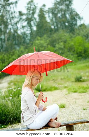 Portrait of sad young girl with umbrella sitting on bench