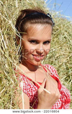 portrait of girl on green meadow near haystack