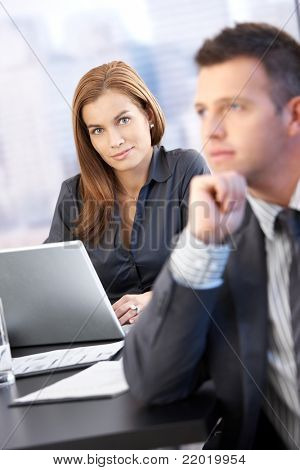 Portrait of beautiful businesswoman smiling in meeting room, man in background.?