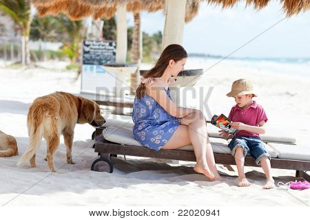 Mother, son and golden retriever dog outdoors at beach