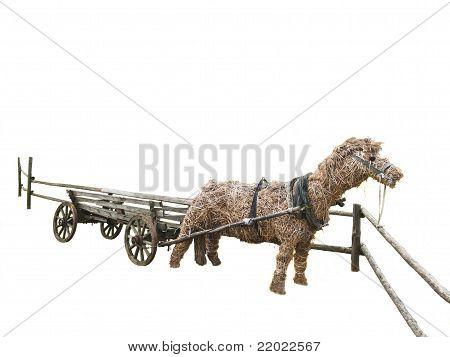 Caballo decorativo heno y paja dibujado por un antiguo carro de madera rural.