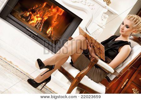Blond lady reading book near fireplace