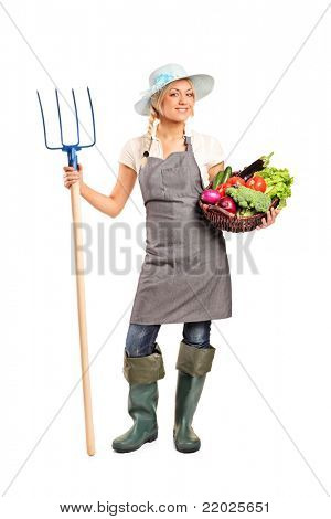 Full length portrait of a female farmer holding a pitchfork and basket with vegetables isolated against white background
