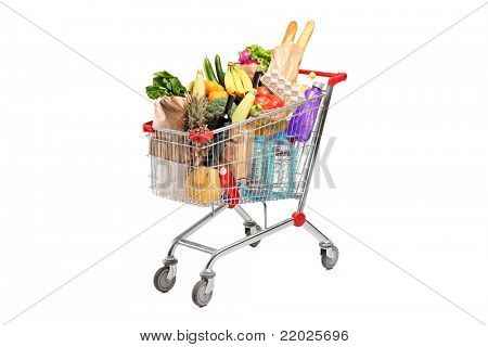 A shopping cart full with various groceries isolated on white background