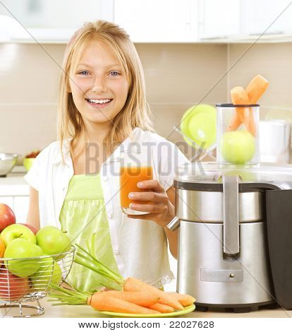 Happy Girl drinking fresh carrot and apple juice. Juice Extractor.