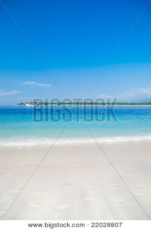Tropic island beach with yacht on background. Gili, Indonesia
