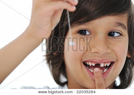 Lost milk-tooth, cute boy with long hair holding his tooth on thread