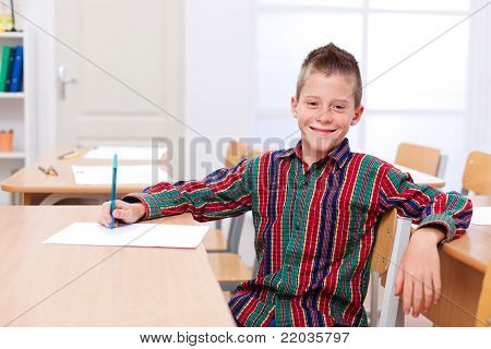 Confident Boy Sitting Alone In Classroom