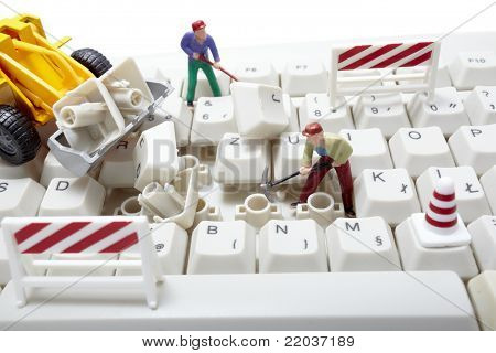 Miniature Toy Workers Repairing Computer Keyboard
