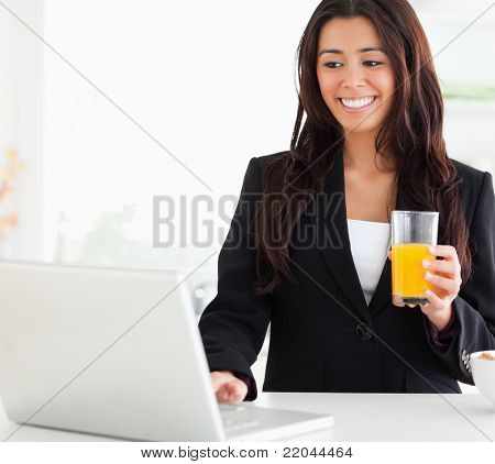 Pretty woman in suit relaxing with her laptop while holding a glass of orange juice in the kitchen