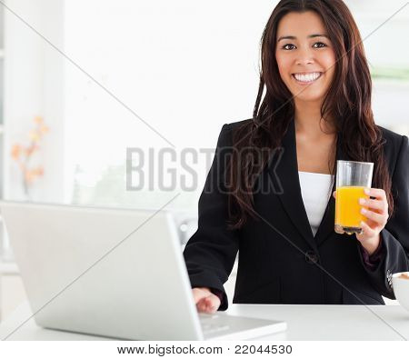 Beautiful woman in suit relaxing with her laptop while holding a glass of orange juice in the kitchen