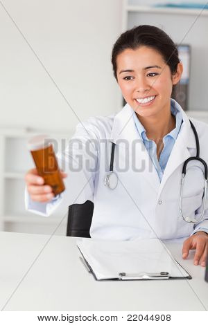 Lovely smiling doctor holding a box of pills while sitting in her office