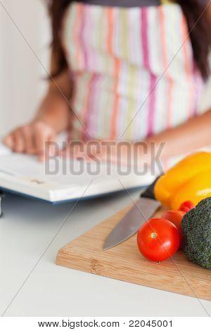 Hembra joven consultoría un cuaderno estando en la cocina