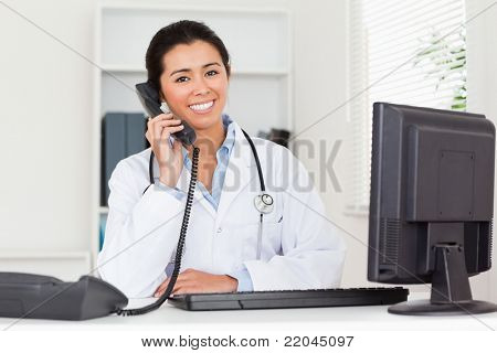 Lovely woman doctor on the phone while sitting in her office