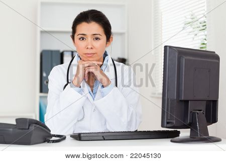 Lovely worried woman doctor looking at the camera while sitting in her office