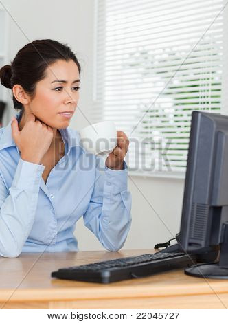 Charming woman enjoying a cup of coffee while looking at a computer screen at the office