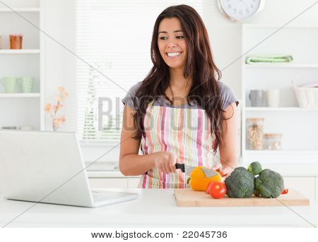 Good looking woman relaxing with her laptop while standing in the kitchen