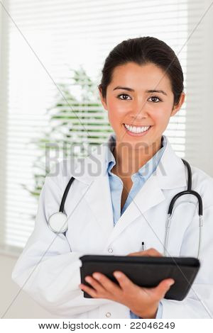 Gorgeous female doctor with a stethoscope writing on a notebook while standing in her office