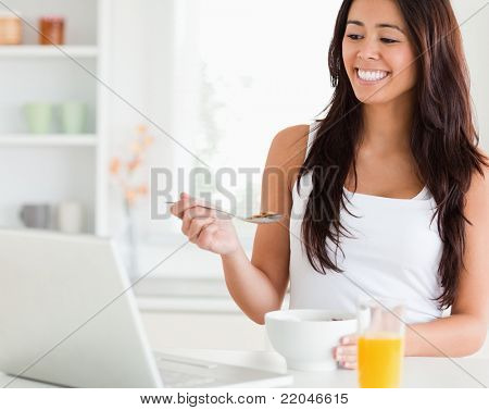 Beautiful woman enjoying a bowl of cereal while relaxing with her laptop in the kitchen