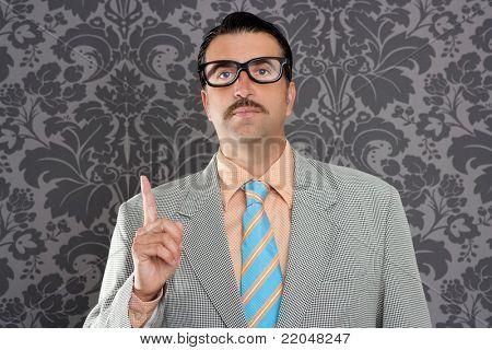 nerd retro teacher raising finger up over vintage wallpaper background