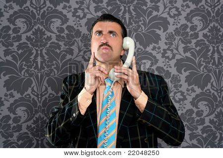 businessman with scared expression talking by  telephone with retro mustache