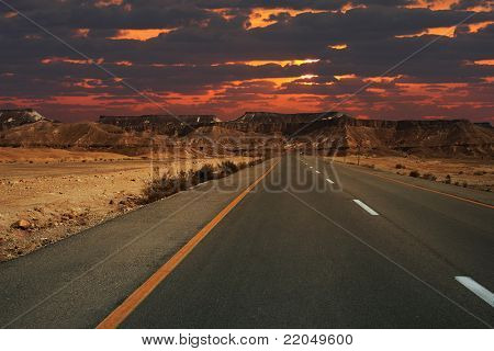 Beautiful sunset over mountains and highway running through Ramon crater in Israel.