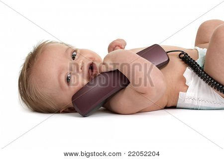 Baby boy laughing and holding a landline telephone reciever