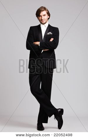elegant young man in black tuxedo, full body shot,  studio shot